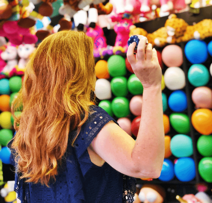 red headed woman throwing a dart at a wall of balloons at the State Fair of Texas