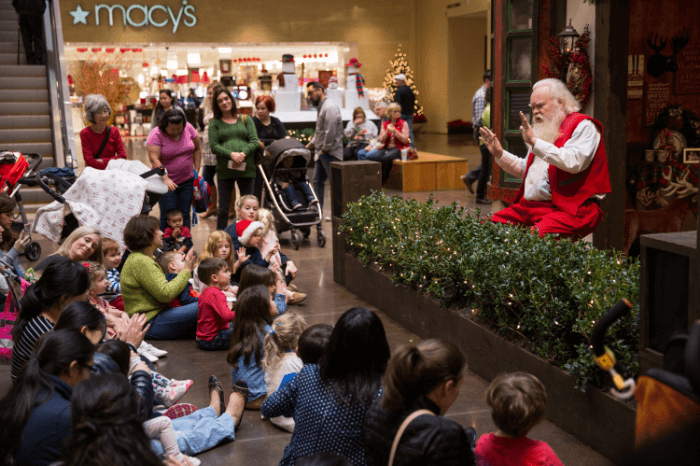 children and parents sitting on the floor of a shopping mall enjoying Story Time with Santa