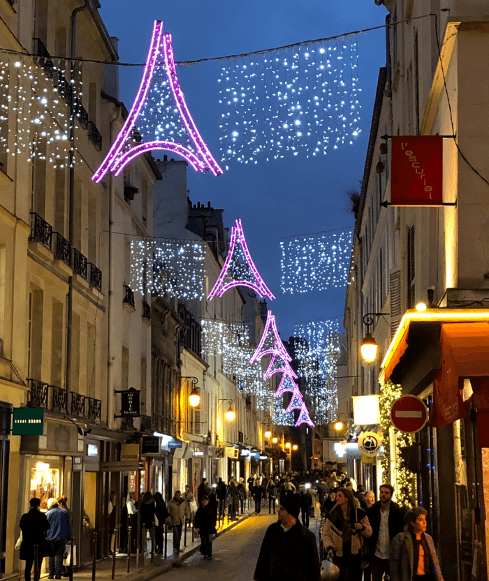 Pink and white twinkle lights in the shape of the Eiffel Tower strung across a street