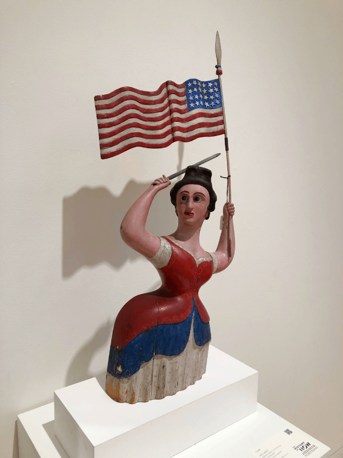 a red, white and blue Folk Art Statue of a lady holding an American Flag and a sword