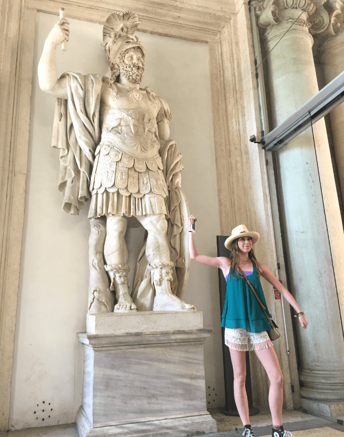 Teenage girl in a green shirt mimicking the pose of a Roman statue of an Emperor