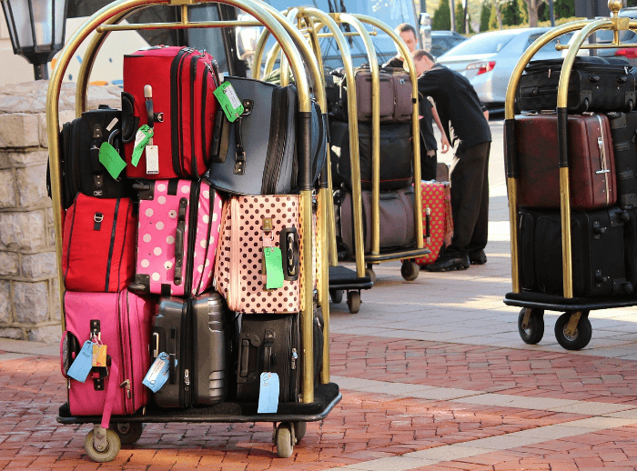 Suitcases stacked on a brass rolling hotel cart