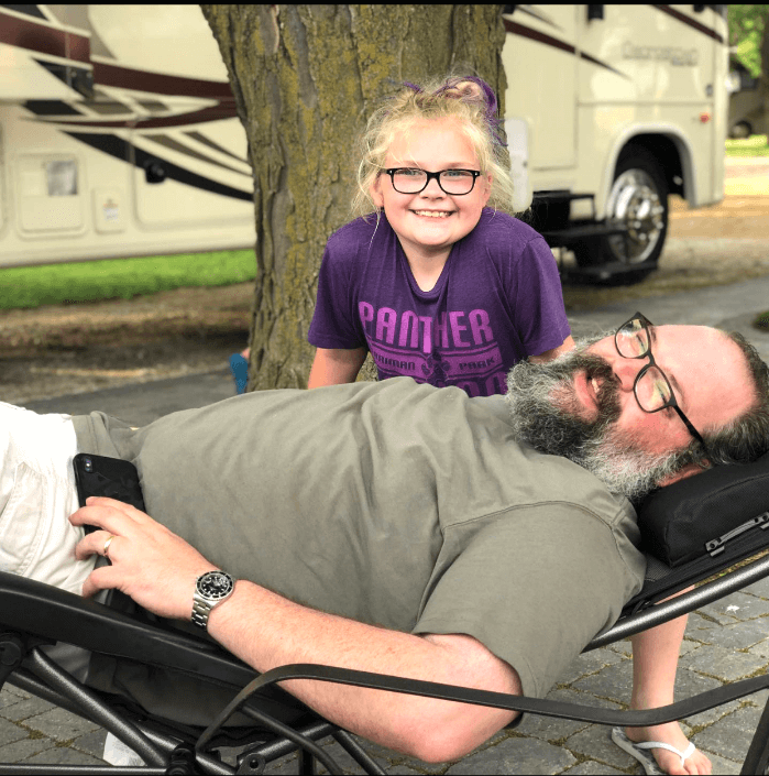 Bearded man lying on his back in a lounge chair with a little girl in a purple shirt leaning over him and smiling