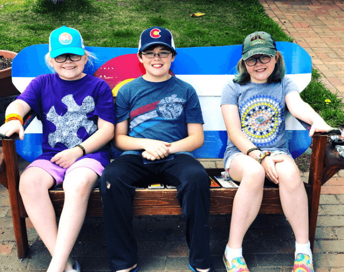 Two young girls and a young boy wearing baseball hats sitting on a bench and smiling