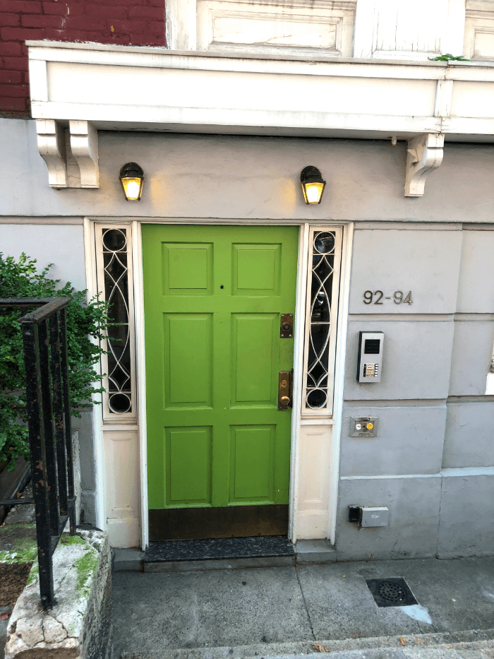 a green door at the bottom of a set of steps