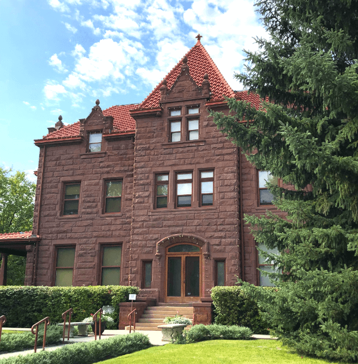 Old two-story brick Moss Mansion in southeast Montana under a blue sky