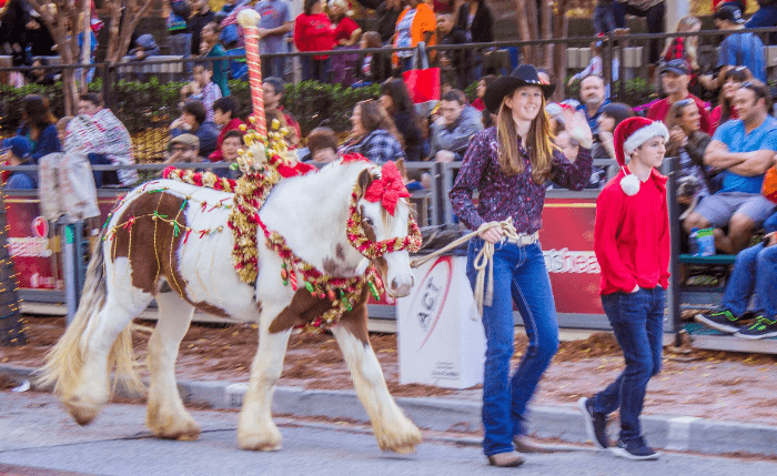 two girls in cowboy hats leading a pony in a downtown Christmas parade