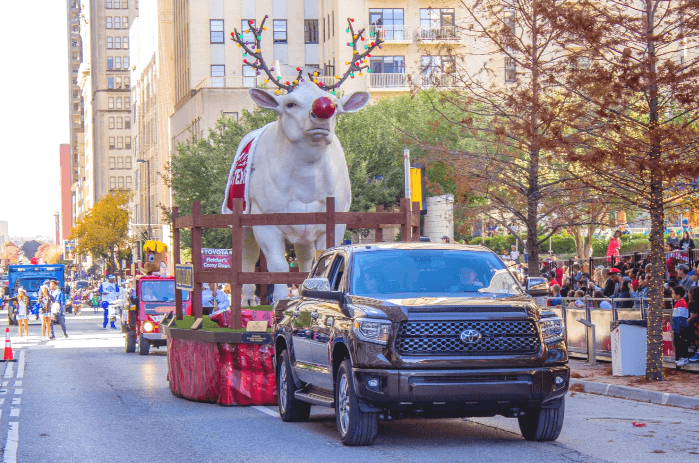 a pickup truck pulling a reindeer float in the Dallas Holiday Parade