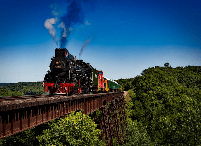 train on a bridge under a bright blue sky