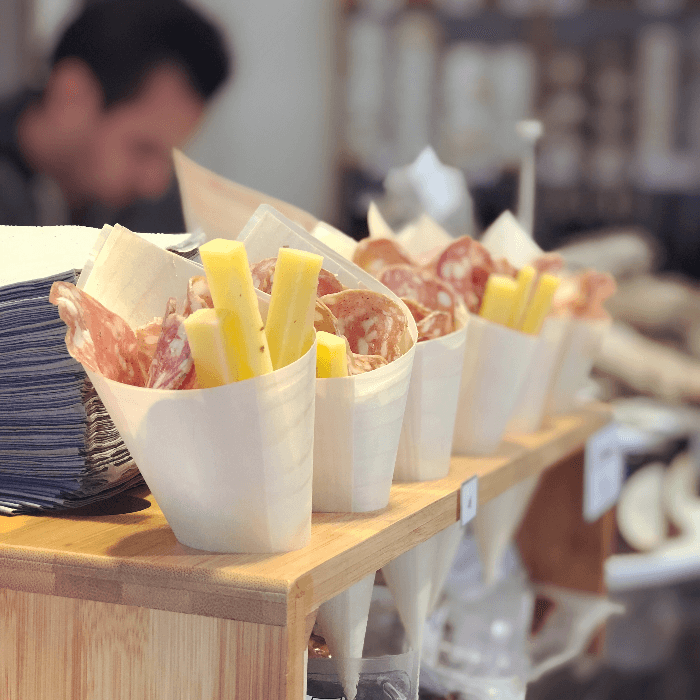 a paper cup filled with salami and cheese slices