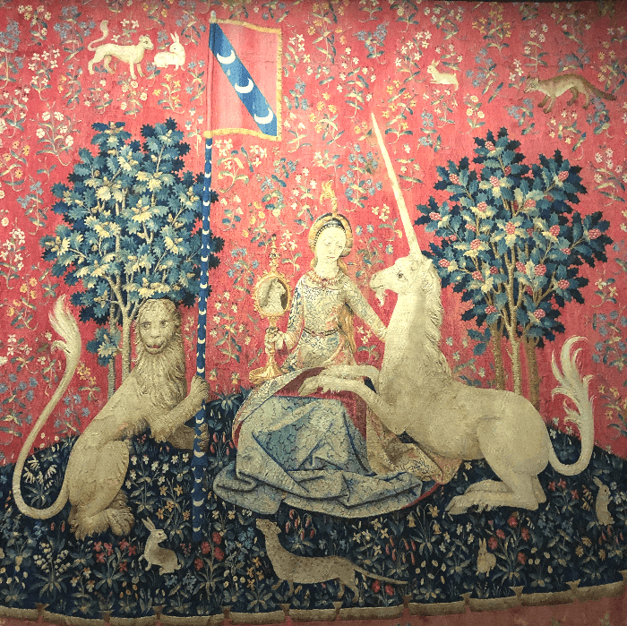 an old red tapestry with a lady and a unicorn