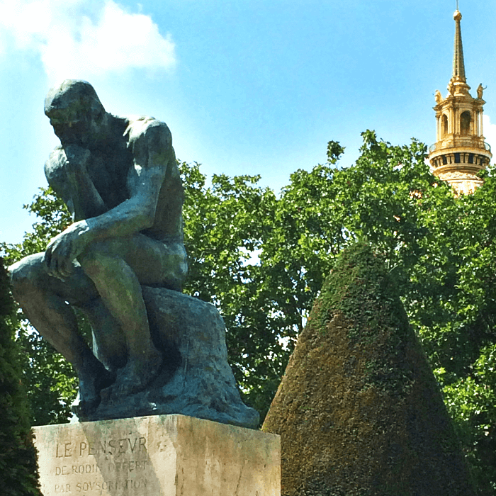a bronze statue on stand under a bright blue sky
