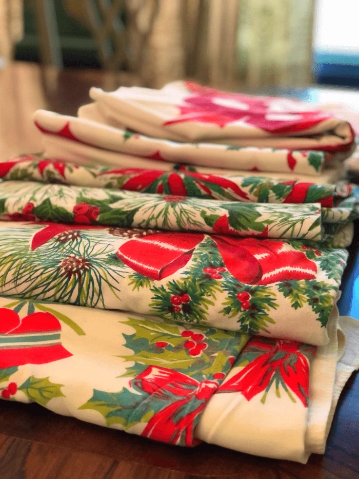 a stack of several Vintage Christmas tablecloths