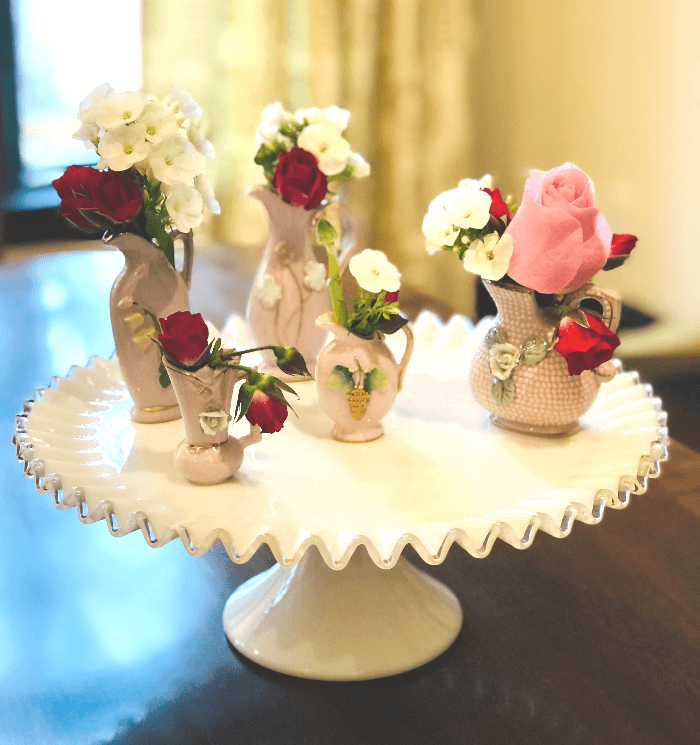a White Cake Plate with Pink Mini Pitchers
