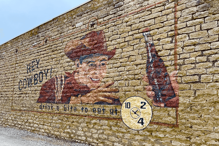a cowboy painted on the side of a brick building