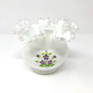 a white ruffled vase with purple violets