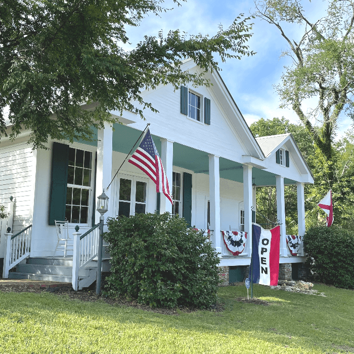 a small white house with columns and an American flag