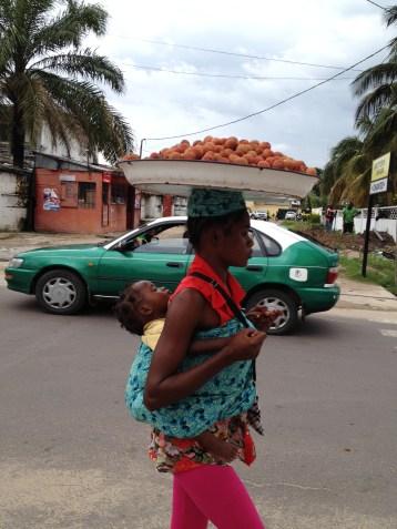 jeune-vendeuse-de-litchis-devant-un-celebre-taxi-vert-de-brazza