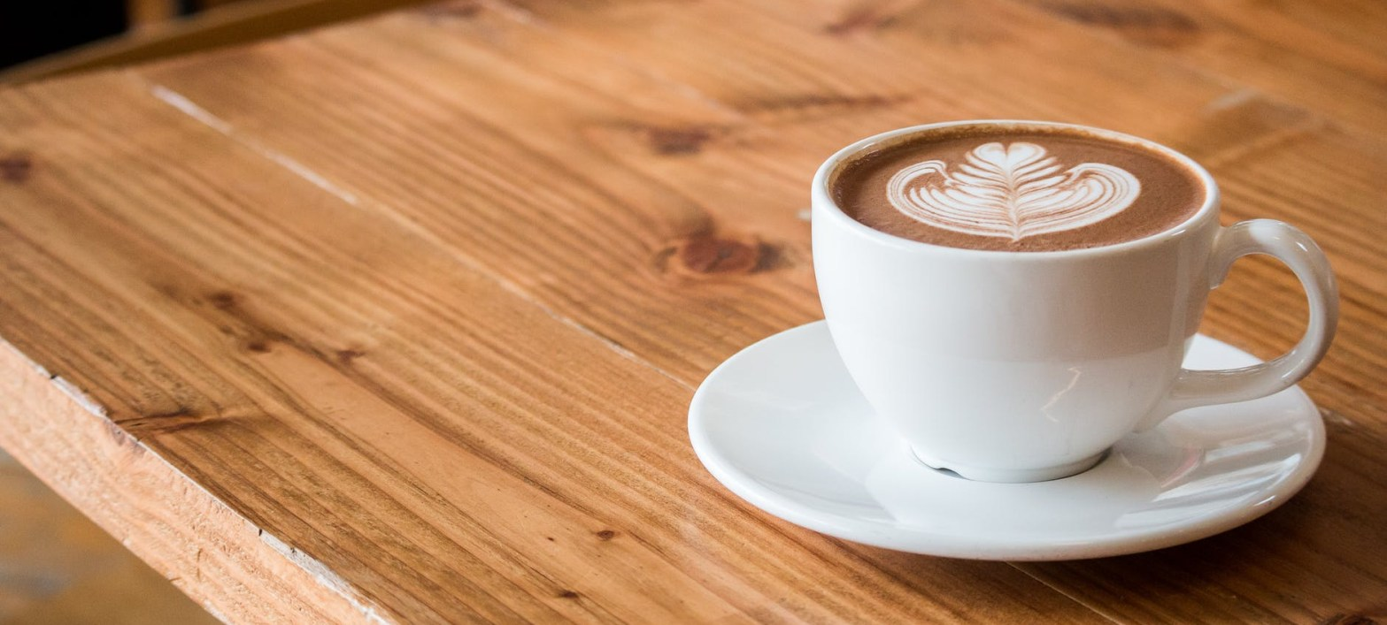 a cup of coffee on wood table