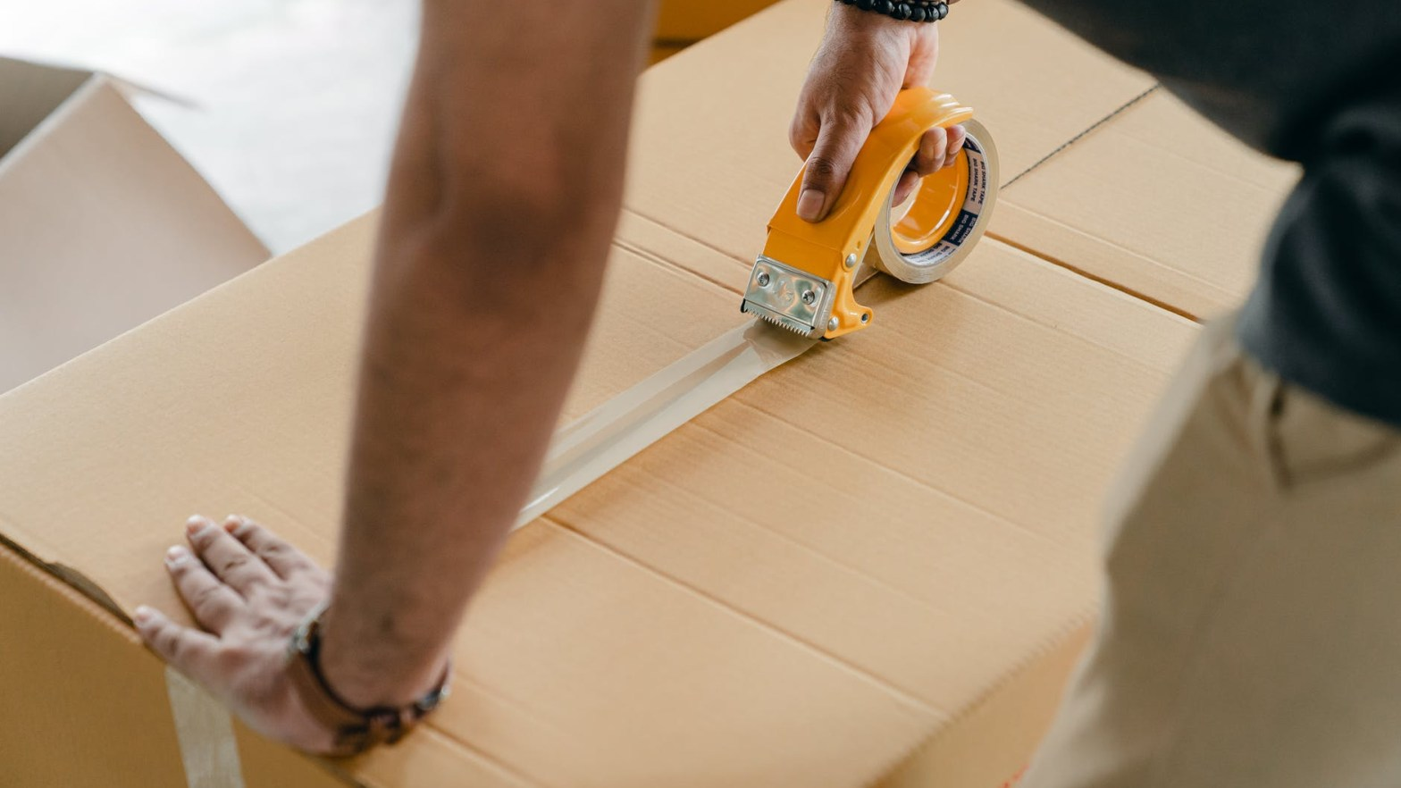 man packing box with scotch tape
