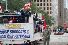 A soldier greets Houston sheriffs on the HSD truck as she passes them. | Sara Samora/The Cougar