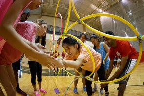 Tau Kappa Epsilon and Chi Omega members help each other maneuver through the course obstacle.