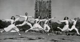 UH cheerleaders dancing mid-leap around an unlit bonfire in 1969.  Courtesy of UH