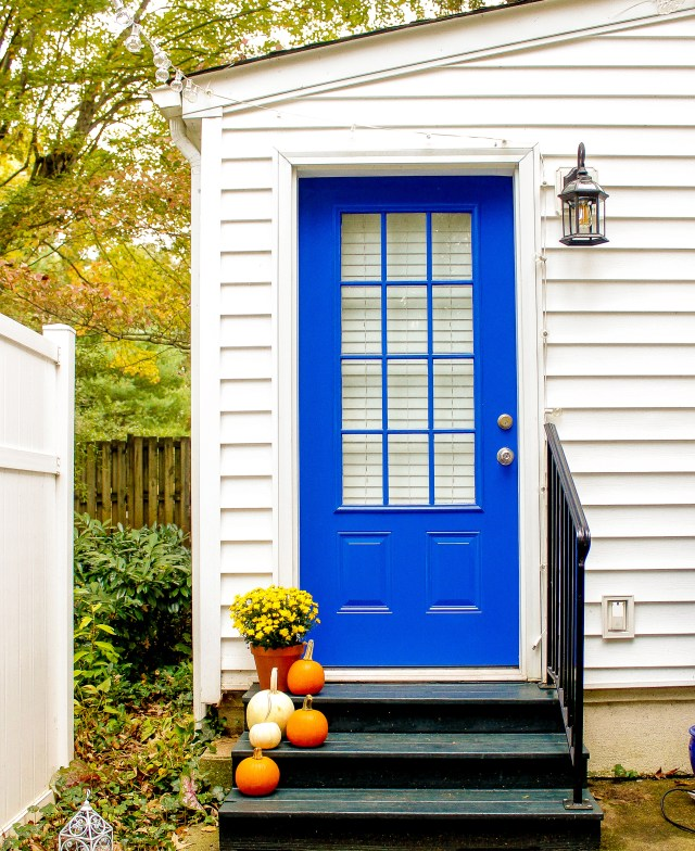 The after picture shows our bright blue door and updated light fixture just after our back porch makeover.