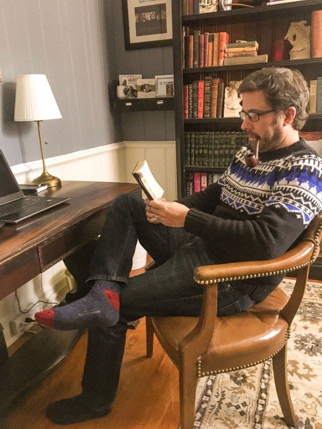 Man sitting at desk smoking pipe and reading a book-- the gift guide suggests things such as an escape room experience or gift certificate to a local bookstore