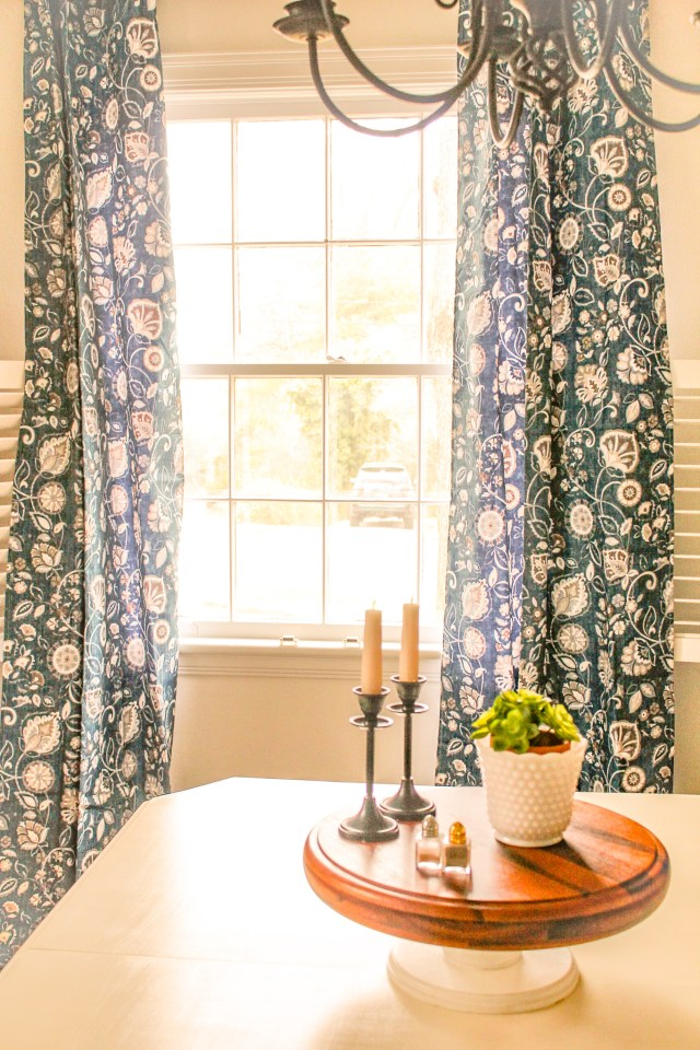 long, blue and white floral curtains framing open window; wood cake stand in foreground on top of antique white dining table, all part of our budget makeover