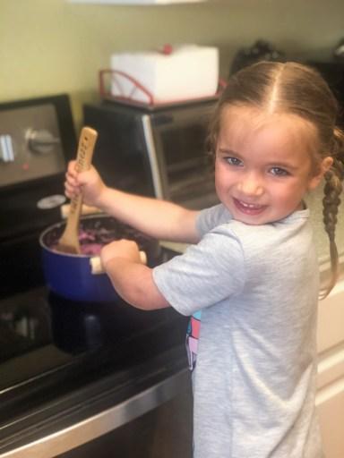 little girl stirring something on the stove