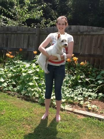 Girl standing in front of garden, holding white dog