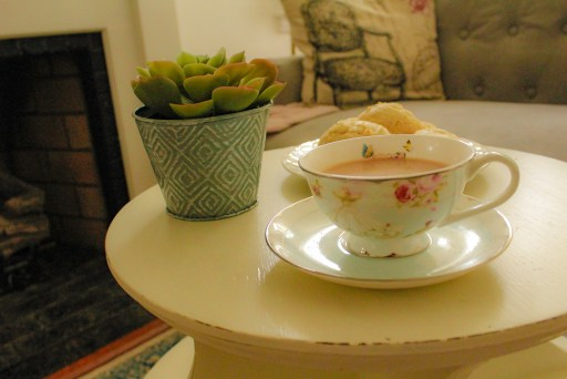 tea cup with cookies and a plant in the background