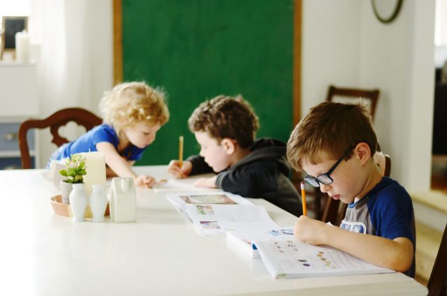 children doing schoolwork at a table