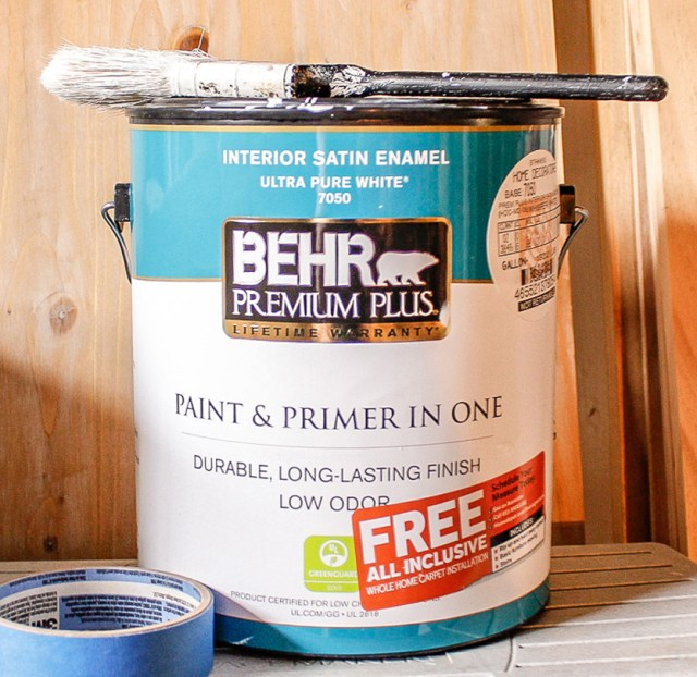 can of paint for the office closet with paint brush on top and roll of painter's tape on the side