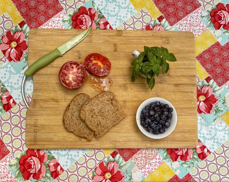 a wooden cutting board sits on a decorative tablecloth. On the cutting board are a sliced tomato, knife, slices of bread, blueberries, and a bunch of fresh basil.