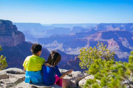 Sibling children sitting by canyon