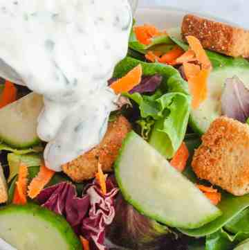 Homemade Ranch Dressing being poured onto garden salad