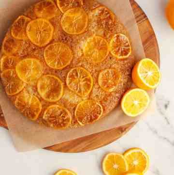 Lemon upside-down cake on wooden tray surrounded by lemon slices