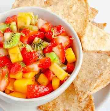 Fruit Salsa in a white bowl alongside homemade cinnamon tortilla chips