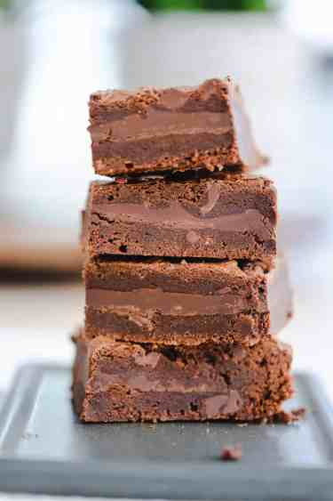 Four brownies are stacked on top of one another. You can see the layers of brownie and smooth chocolate bar in each.