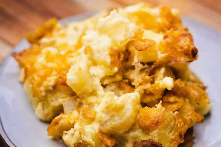 A serving of Funeral Potatoes sits on a plate ready to enjoy.
