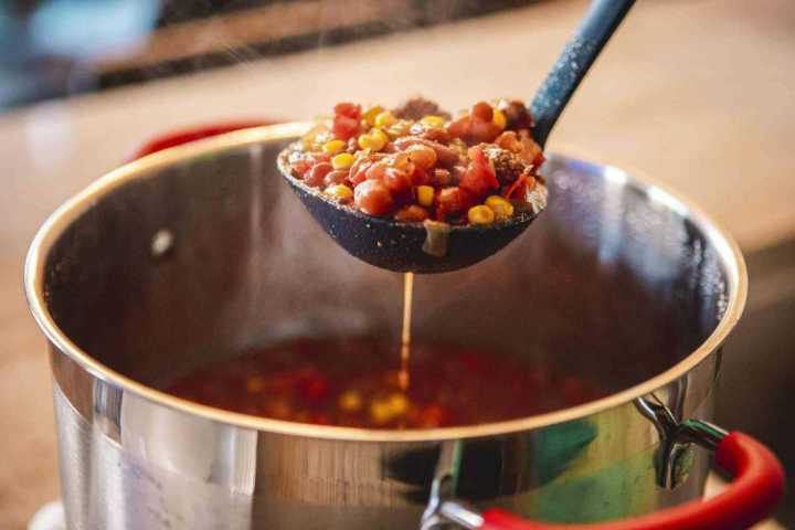 A ladel is filled with sweet and spicy chili, being pulled from a large silver pot.