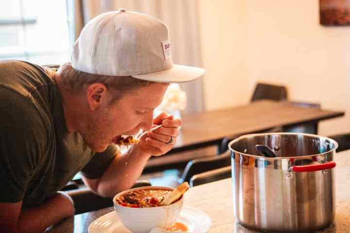 Dallin, a middle age man, leans over a bowl of hot sweet and spicy chili taking a bite.