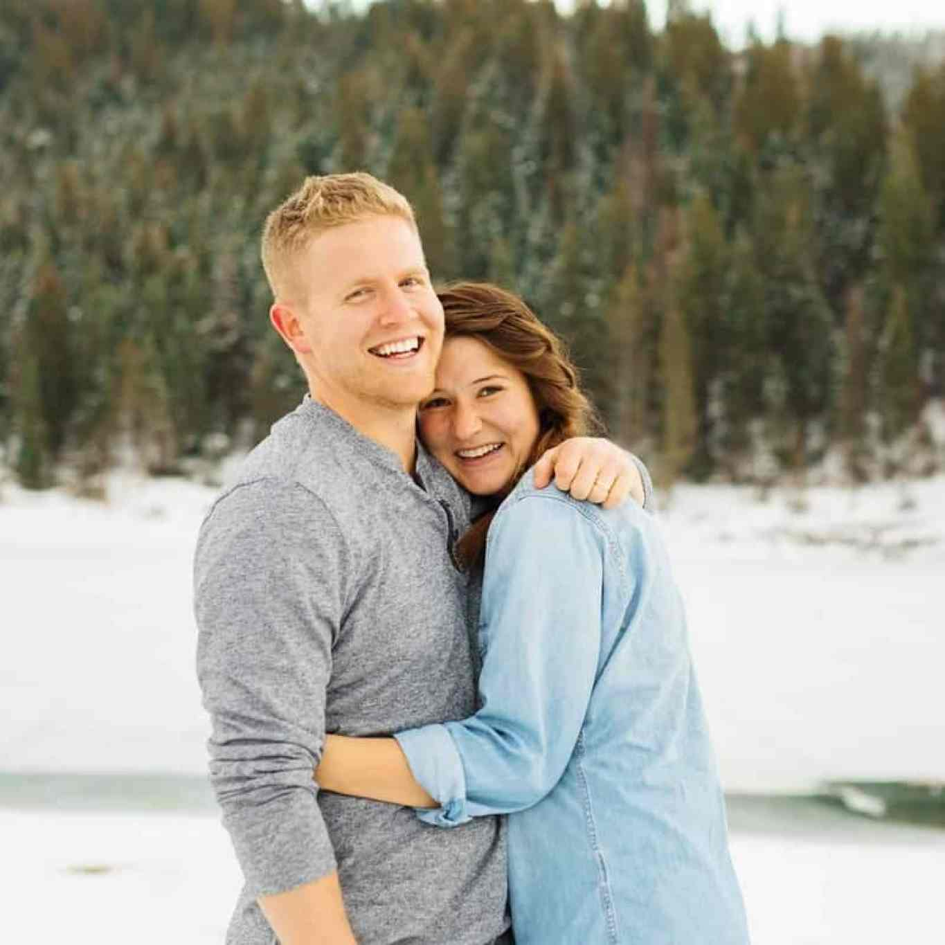 Dallin and Ashley stand hugging in front of a line of trees and snow on the ground.