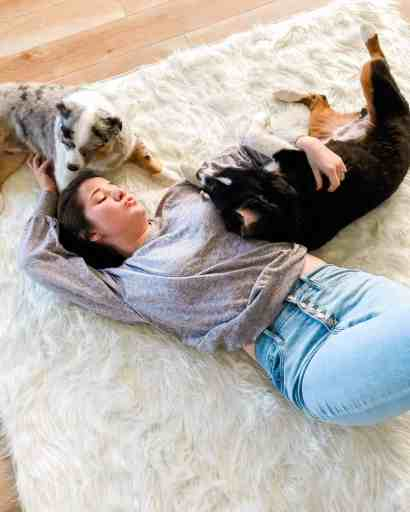 Ashley, creator of family friendly recipes, lay on shaggy white rug with Luna and Dash.