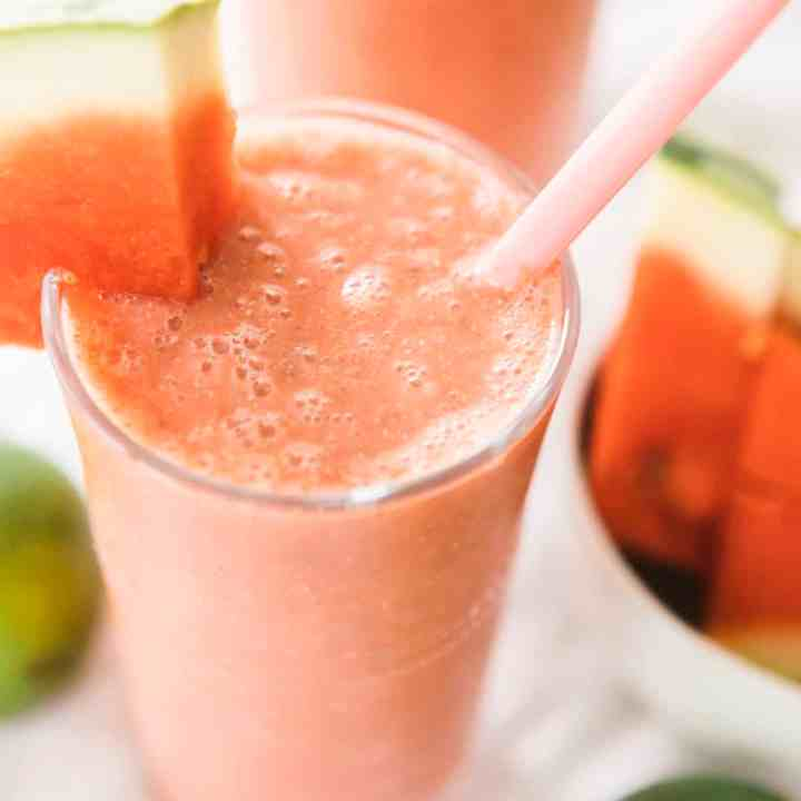 Glass of Watermelon Smoothie is sitting ready to enjoy. Wedge of watermelon hangs off the side with a pink silicone straw in glass.