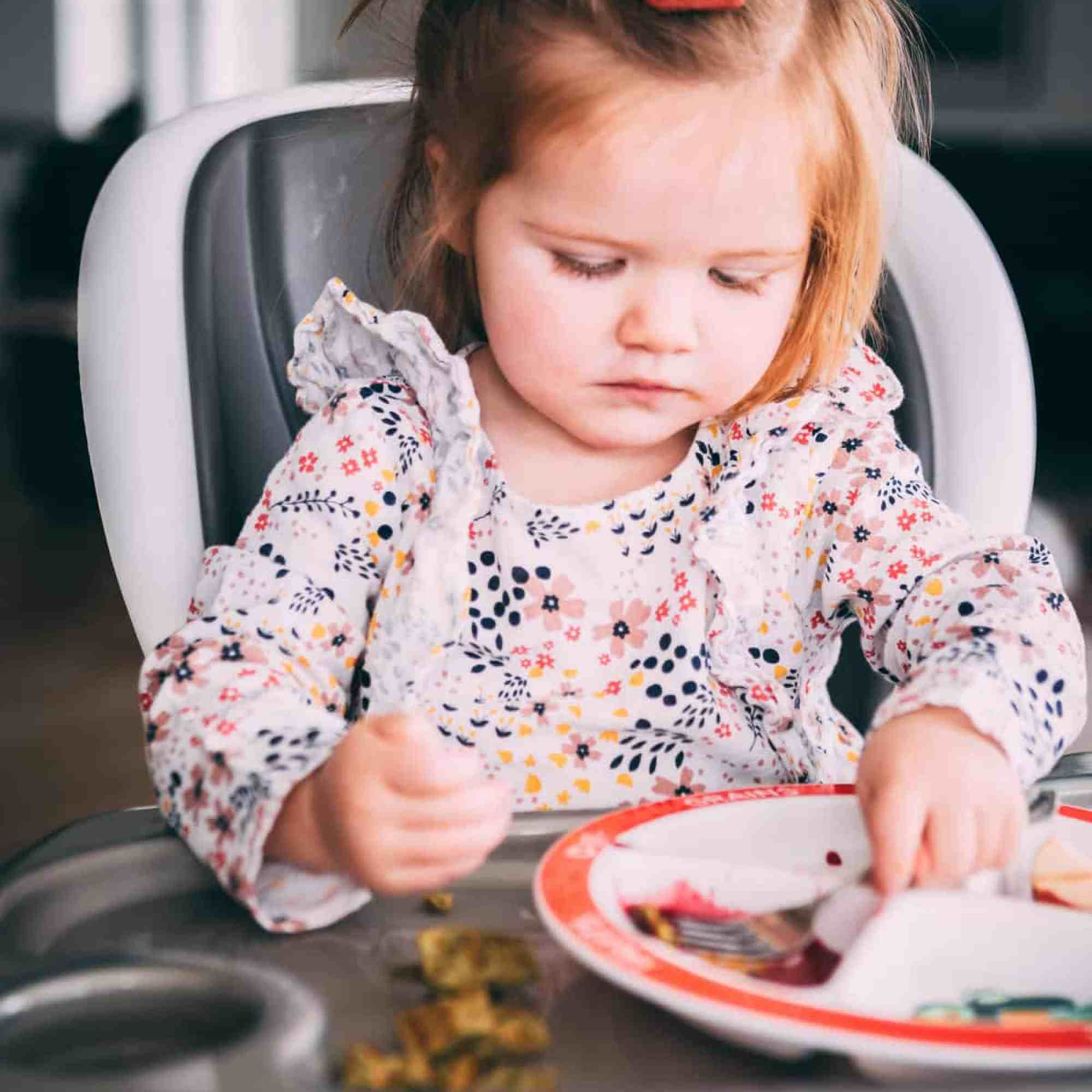 James sits in her highchair looking down at her plate to eat a cut up waffle.