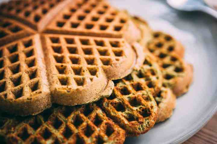 Closeup of three heart shaped green and golden brown smoothie waffles sit on a plate.