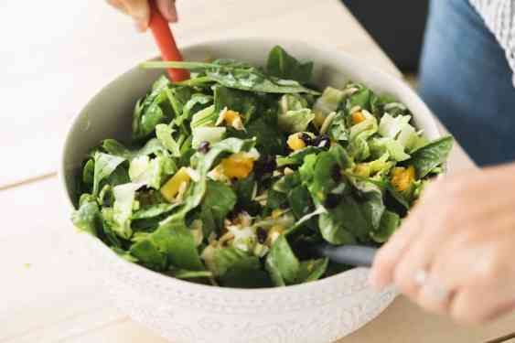 Citrus and Cranberry winter salad is in large white bowl. Ashley holds to spoons tossing the salad to combine.